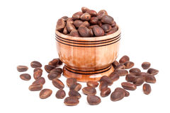 Unpeeled cedar nuts in a wooden barrel on white background Royalty Free Stock Photo