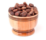 Unpeeled cedar nuts in a wooden barrel on white background Stock Image
