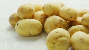 Unpeeled clean potatoes in closeup. Closeup shot of pile of unpeeled clean potatoes composed on white surface in daylight stock footage