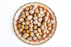 Unpeeled hazelnuts plate Stock Photography