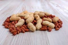 Unpeeled och skalade jordnötter på köksbordet Fotografering för Bildbyråer
