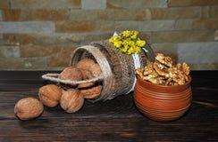Unpeeled och skalade valnötter i en kruka i form av en korg och i en lerakruka på en trätabell royaltyfri bild