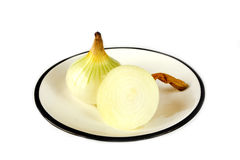 Unpeeled onions on plate against white background Stock Photography