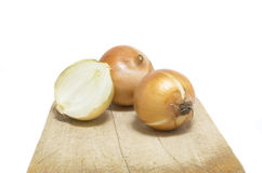 Unpeeled Onions Sit On An Isolated Chopping Board Royalty Free Stock Photography