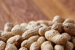 Unpeeled peanuts on a wooden background, top view, selective focus, shallow depth of field. Some copy space for your text. Studio shot. Organic nutritious stock photo