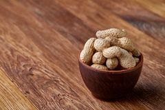 Unpeeled peanuts on a wooden background, top view, selective focus, shallow depth of field. Some copy space for your text. Studio shot. Organic nutritious royalty free stock photos