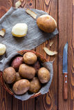 Unpeeled and peeled potatoes in a basket and a knife Stock Images