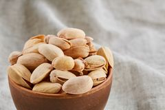Unpeeled pistachios in ceramic bowl closeup, selective focus. Composition of raw unpeeled pistachios in clay ceramic bowl on light grey cotton tablecloth or royalty free stock photography
