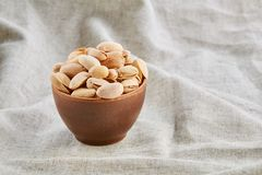 Unpeeled pistachios in ceramic bowl closeup, selective focus. Composition of raw unpeeled pistachios in clay ceramic bowl on light grey cotton tablecloth or stock photo