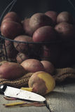 Unpeeled Potatoes in a Basket with Knife Stock Photo