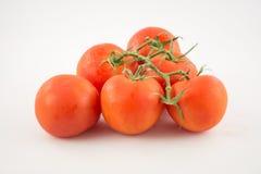 Unpeeled sex, nya röda tomater med gröna svansar på vitbaksida Arkivfoto