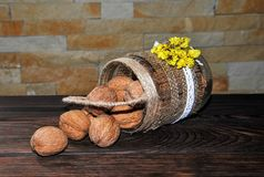 Unpeeled walnuts in a can in the form of a basket on a wooden table. stock image