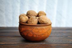 Unpeeled walnuts in pottery on a table stock images