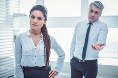Unpleasant boss failing in understanding problem with his colleague. Confused superior. Unpleasant boss failing in understanding problem with his female stock photo