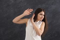 Unpleasant feeling, woman expressing disgust. Unpleasant feeling. Woman expressing disgust, grimacing and gesturing on gray studio background Stock Image