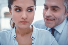 Unpleasant man whispering in ear of his female coworker. Vulgar whisper. Unpleasant men whispering in ear of his scared good-looking female coworker royalty free stock photography