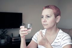 Unpleasant pain. Sad unhappy beautiful woman sitting at the table. Depression and headache. Takes a pill and washes down with. Water stock images