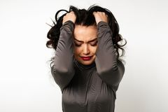 Unpleasant pain. Sad unhappy handsome woman holding his forehead while having headache stock photography