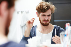 Unpleasant procedure. Young man looking at cotton-bud while cleaning his ears royalty free stock photo