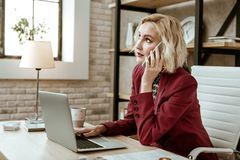 Unpleasant short-haired businesswoman rolling her eyes during conversation. Aggressively talking. Unpleasant short-haired businesswoman rolling her eyes during stock photo