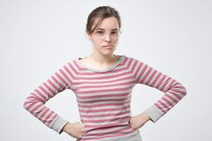 Unpleasant young lady in pulover holding hands on hips. Confused woman expressing disgust and looking at camera. Unpleasant young lady in pulover holding hands royalty free stock images