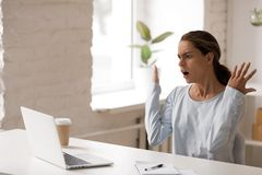 Unpleasantly surprised woman looking at laptop screen, bad news. Unpleasantly surprised woman looking at laptop screen, sitting with raised hands, gesture stock photos