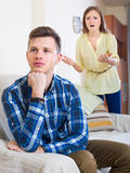 Unpleased person criticizing  spouse. Person criticizing young spouse in living room Royalty Free Stock Photo