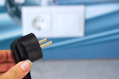 Unplug or plugged in concept,hand holding electric plug.  royalty free stock photos
