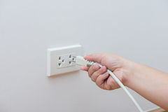 Unplug or plugged in concept. Hand holding and pull electric plug stock image