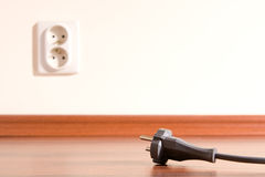 Unplugged. Two pin plug on the floor and electrical outlet in background royalty free stock photography