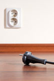 Unplugged. Two pin plug on the floor and electrical outlet in background Stock Image