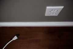 Unplugged Cord On Floor Beside Electrical Outlet Stock Image