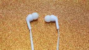 Unplugged white headphone golden background stock photography
