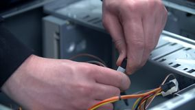Unplugging wires inside of personal computer. Close up of hands disconnecting cables inside personal computer in slow motion stock footage
