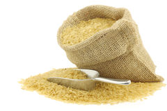 Unpolished rice (whole grain) in a burlap bag. With an aluminum scoop on a white background stock photos