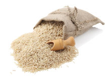 Unpolished rice. (whole grain) in a burlap bag with an wood scoop on a white background Stock Images