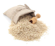 Unpolished rice. (whole grain) in a burlap bag with an wood scoop on a white background Royalty Free Stock Image