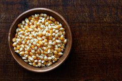Unpopped popcorn in dark wooden bowl isolated on dark brown wood Royalty Free Stock Photography