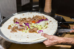 Unprepared turkish grilled traditional dish Doner Kebab on a metal plate. With chicken meat or skewed lamb mutton in hand of cook in the kitchen of a restaurant Stock Image