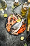 Unprocessed seafood, dorado, shrimp with white wine and spices. On a rustic background Stock Photography