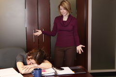 Unproductive. A tired employee sleeps and the boss is upset stock photo