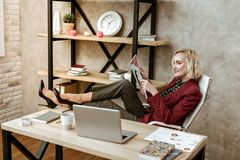 Unprofessional short-haired woman putting her legs on office table stock photo
