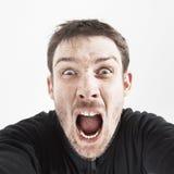 Unrasierter Mann in einer schwarzen Jacke auf einem weißen Hintergrund schreit Stockbild