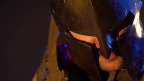 Unrasierter römischer Gladiator im Sturzhelm und in der Rüstung hält rostige Klinge auf seiner Schulter stock footage