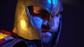 Unrasierter römischer Gladiator mit einer Narbe auf seinem Gesicht in einem Sturzhelm und in einer Rüstung steht mit seinem zurüc stock video footage