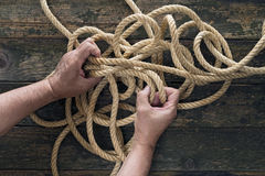 Unraveling. Two hands trying to untangle a rope. Wooden background Royalty Free Stock Photography