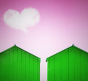 Unreal abstract. Colorful abstract  two green cabin with magenta sky and a cloud in the shape of heart on the background Royalty Free Stock Images