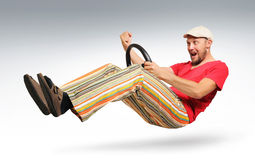 Unreal bearded man car driver. In striped trousers and sandals, a cap, Yes drive concept Stock Image