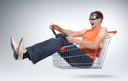 Unreal crazy driver in a shopping-cart with wheel. Concept car shopping Royalty Free Stock Image