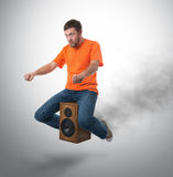 Unreal flying man on wooden speaker Royalty Free Stock Photos